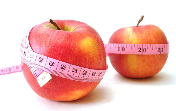 apples with pink tape measure over white background (concept of