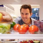 Man Looking Inside Fridge Full Of Food And Choosing Apple