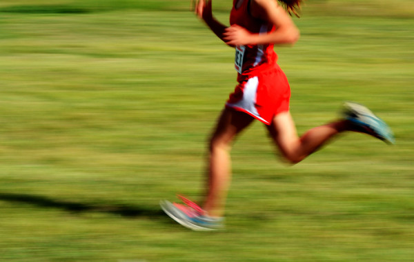 Runner wearing red running a race with fast motion