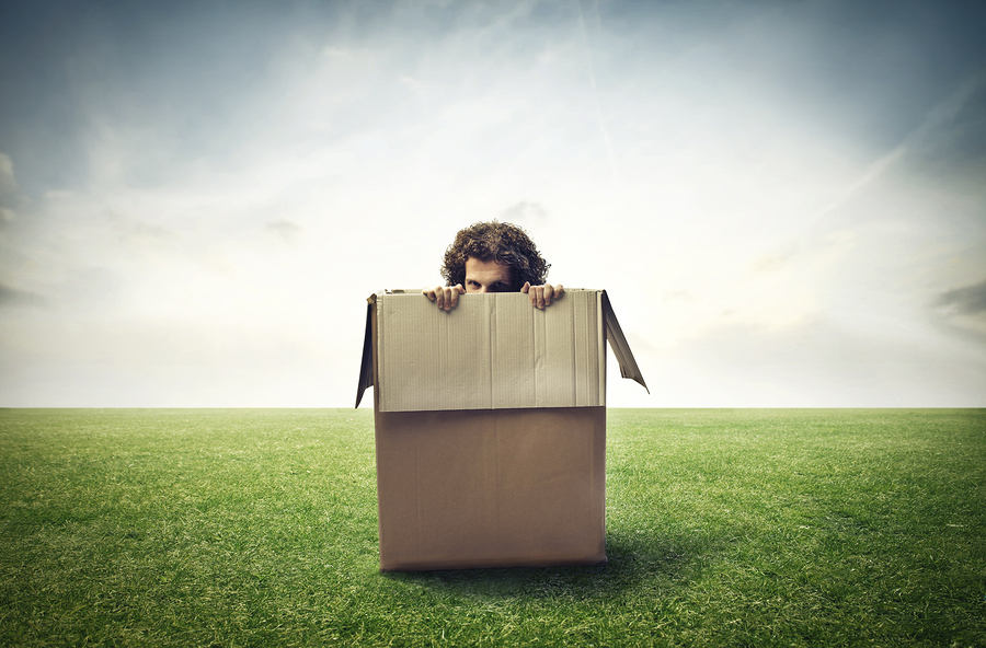 Man hiding behind a box in a large grace field