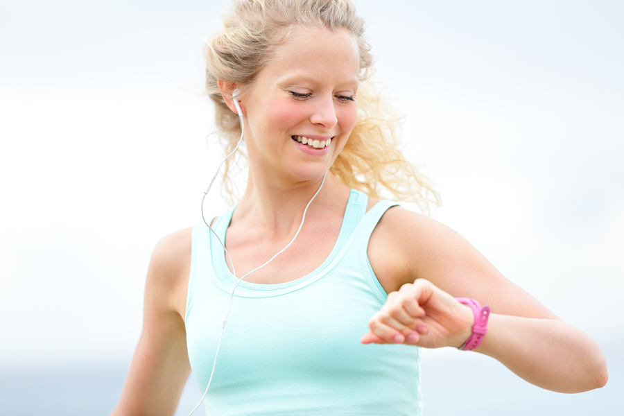 Running woman looking at heart rate monitor watch outside joggin
