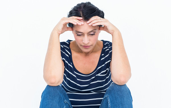 Sad woman sitting with head in hands on white background