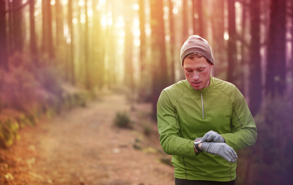 Trail running runner looking at heart rate monitor watch running