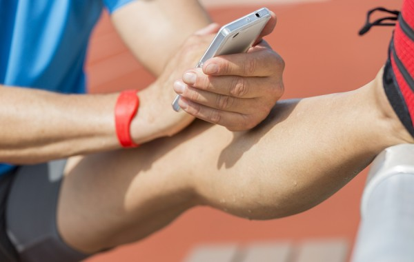 Sweating athlete is stretching after training and checks his fitness results on his smart phone. He wears a fitness tracker wristband on his right arm.