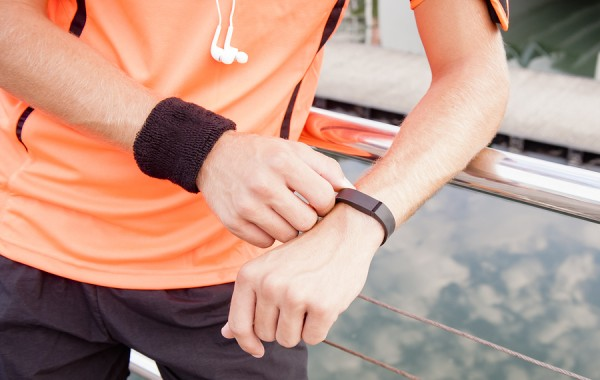 Close up view of guy using fitness device outdoors at sunrise