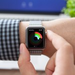 Alushta Russia - August 11 2015: Man hand in Apple Watch with app Activity on the screen and Macbook. Apple Watch was created and developed by the Apple inc.