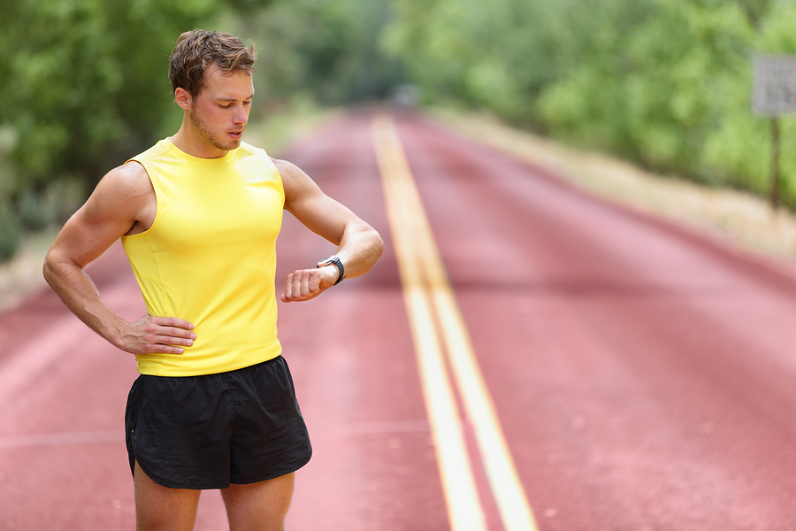 Runner looking at smartwatch heart rate monitor having break while running. Man jogging outside looking at sports smart watch during workout training for marathon. Fit male fitness model in his 20s.