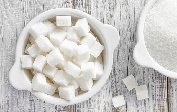 White sugar in a bowls on a wooden table