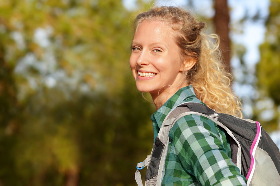 Hiking woman portrait smiling happy in forest. Female hiker girl trekking wearing backpack outside looking candid and fresh at camera. Beautiful young blonde girl living healthy lifestyle.