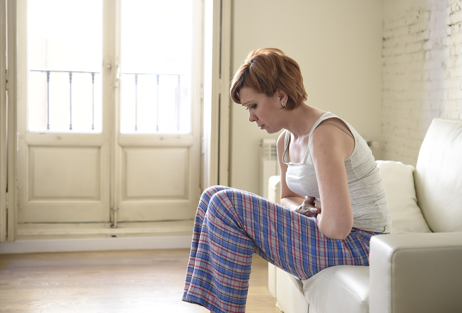 young beautiful red hair woman holding hurting tummy suffering stomach cramp and period pain sitting on home couch in painful face expression female menstruation concept