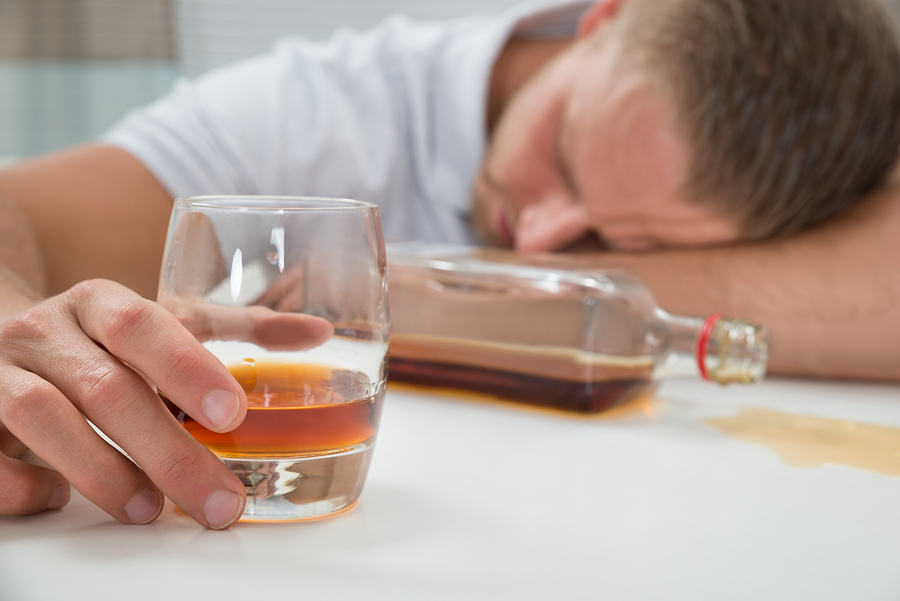 Young Drunk Man Sleeping On Table With A Glass Of Liquor