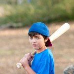 Portrait Of Sad Baseball Boy With Wooden Bat