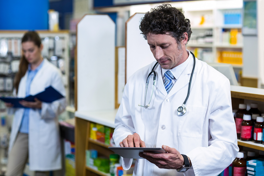 Pharmacist using digital tablet in pharmacy